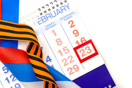 23 February Defender of the Fatherland Day calendar with red framed date, Russian flag, St. Georges ribbon. Close up. White background isolated. Top view. Selective focus. Copy space. Greeting card