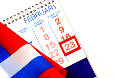23 February Defender of the Fatherland Day calendar with red framed date and Russian flag. Close up. White background isolated. Top view. Selective focus. Text copy space. Festive greeting card concept