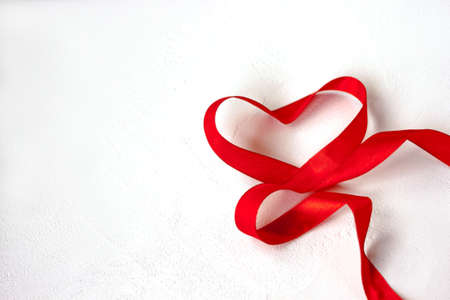 Valentines day blank greeting card heart made of red color satin ribbon on white background isolated lose up top view. Selective soft focus. Text copy space. Holiday 14 February postcard concept Banque d'images