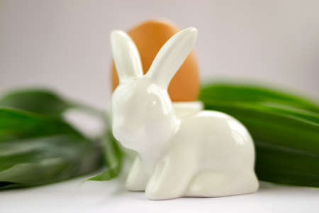 Spring easter composition with ceramic porcelain rabbit bunny salt shaker, egg at eggstand on white table background. Easter concept. Selective soft focus. Shallow depth of field. Text copy space.