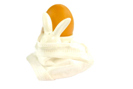 Easter rabbit salt shaker in white medical protective mask with egg at eggstand isolated on white background Coronavirus Easter concept. Selective soft focus. Shallow depth of field. Text copy space.