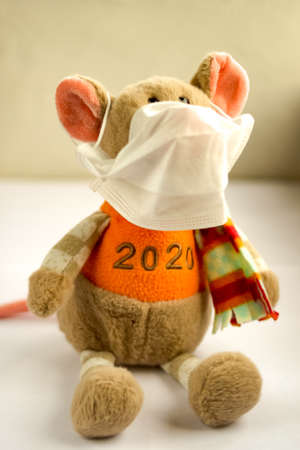 Soft toy mouse in medical face mask on light background. Coronavirus covid-2019 concept. Close up view. Selective soft focus. Shallow depth of field. Text copy space. Standard-Bild