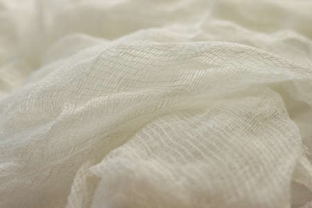 white color woven cotton gauze fabric background texture. close up top view. Selective soft focus. Shallow depth of field. Text copy space.