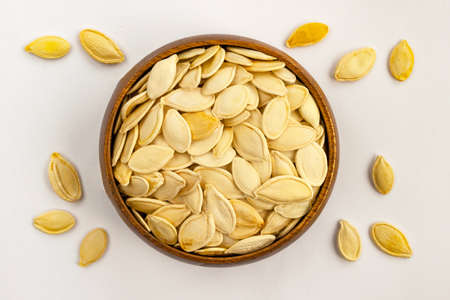 Unpeeled white color pumpkin seeds poured from bamboo bowl on white background. Close up top view. Selective soft focus. Shallow depth of field. Text copy space. Reklamní fotografie