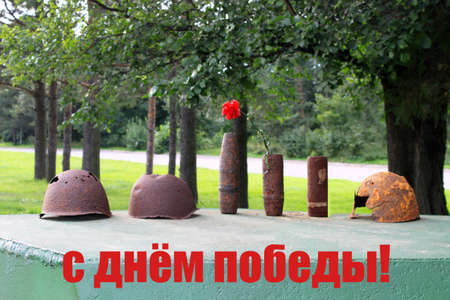 9 May greeting card. Happy Victory Day - text sign translation from Russian language. Rusty helmet, cartridges, flower on natural background.