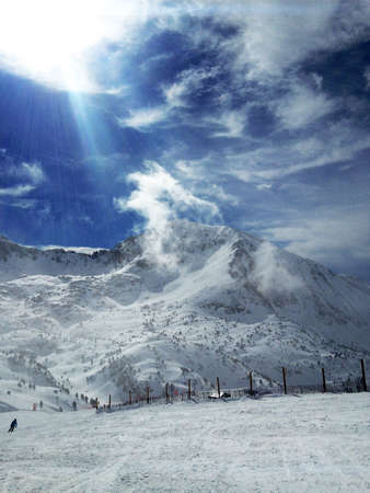 Ski slope with skiers at ski resort in Eastern Pyrenees, Andorra panoramic view, sunny winter day, clear blue sky on white snow and mountain peak background