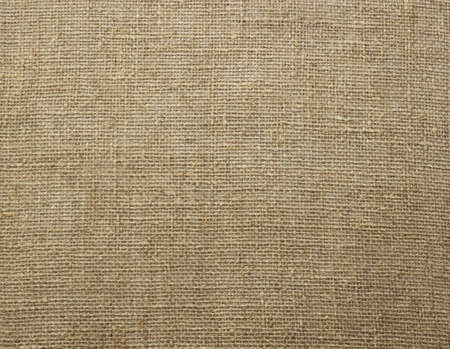 Natural linen raw uncolored textured sacking burlap background. Hessian sackcloth canvas woven texture. Close up. Selective soft focus. Shallow depth of field. Text copy space.
