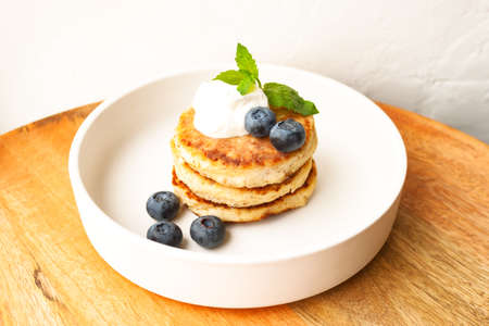 Cottage cheese pancakes or curd fritters stack with sour cream, mint leaf and blueberry in white plate 写真素材