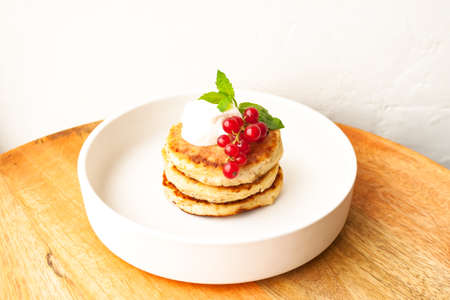 Cottage cheese pancakes or curd fritters stack with sour cream, mint leaf and red currant in white plate 写真素材