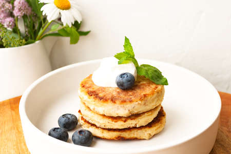 Cottage cheese pancakes or curd fritters stack with sour cream, mint leaf and blueberry in white plate 写真素材 - 152061312