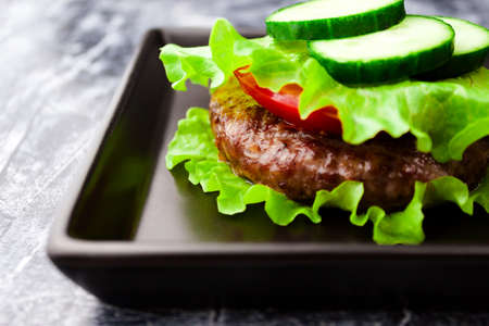 Keto paleo bunless burger lettuce wrapped no bread stacked with beef meat cutlet, tomato, cucumber. Close up. Selective soft focus. Shallow depth of field. Text copy space.