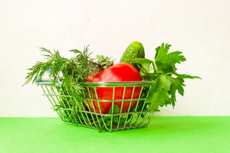 Shopping grocery cart metal on green background. Food basket concept. Close up. Copy space. Flat Lay