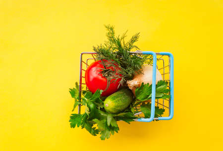 Shopping grocery cart metal on yellow background. Food basket concept close up. Copy space. Flat Lay