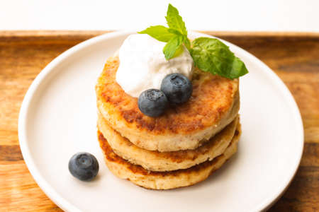 Cottage cheese pancakes or curd fritters stack with sour cream, mint leaf, blueberry, white plate 写真素材