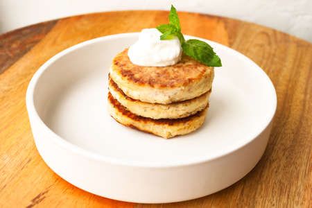 Cottage cheese pancakes or curd fritters stack with sour cream mint decorated in white plate 写真素材