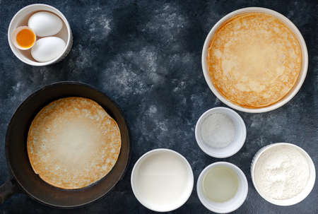 Homemade crepes pancakes in cast iron pan and cooking ingredients over rustic black background