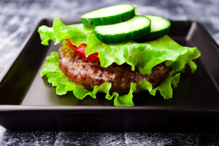 Keto paleo bunless burger lettuce wrapped no bread stacked with beef meat cutlet, tomato, cucumber. 写真素材