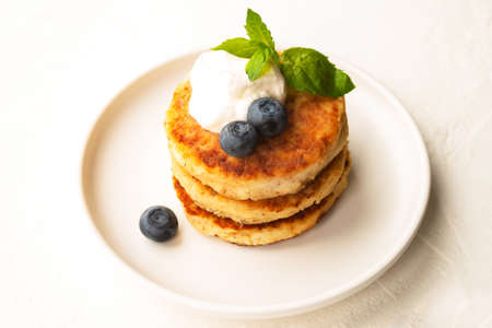 Cottage cheese pancakes or curd fritters stack with sour cream, mint leaf, blueberry in white plate 写真素材