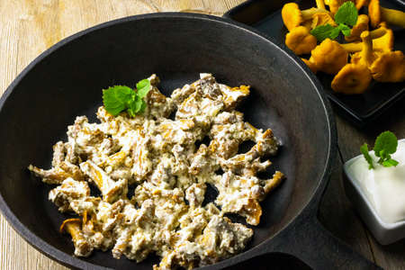Chanterelle wild mushrooms fried with sour cream sauce in cast iron pan on vintage wooden background