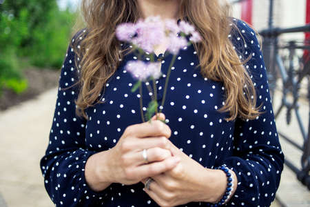 Closeup of unrecognizable caucasian young brunette female hands holding wild flowers bouquet in hand 写真素材