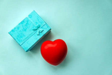Valentine day concept with turquoise gift box with ribbon and red heart on pastel blue background.