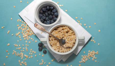 Oatmeal porridge with fresh blueberries in white bowl on blue background, linen napkin, silver spoon
