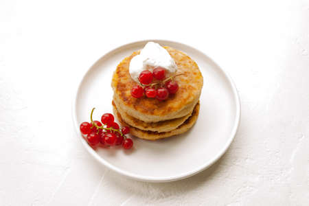 Cottage cheese pancakes or curd fritters stack with sour cream and red currant in white plate
