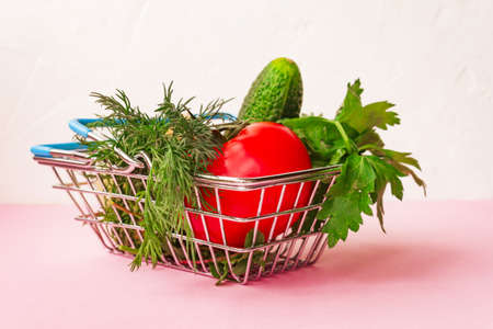 Shopping grocery cart metal on pink background. Food basket concept. Close up. Copy space
