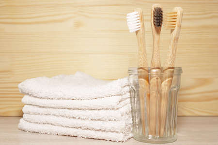 Family set of tree bamboo toothbrushes in glass bowk, white towels on wooden background. Eco friendly concept