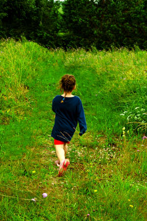 Cute Little girl kid with brown hair in a braid dressed in blue and red running on grass. Back view 写真素材 - 154814642