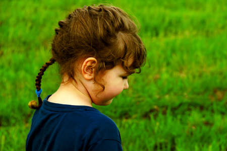 Cute girl brown hair in a braid, dressed in blue, stands in profile on green grass background