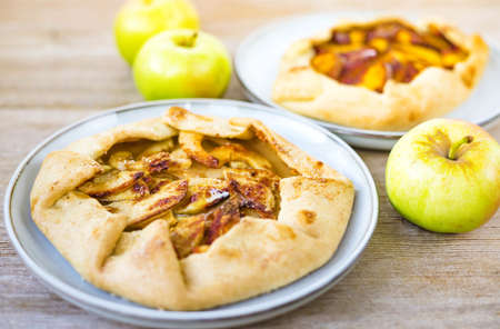 Apple galette with sweet fruit filling on rustic natural wooden background. Autumn open pie concept