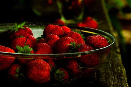 Fresh strawberries ripe in glass bowl on dark moody rustic background. Dark food photography