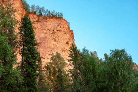 Rock stone Vetlan, Ural mountains, Krasnovishersk, Perm region, Russia in sun rays at sunset in summer view from below on natural landscape background. Text copy space. 스톡 콘텐츠