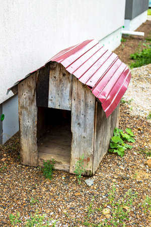Old rural empty wooden dog house kennel with red roof in the courtyard 写真素材