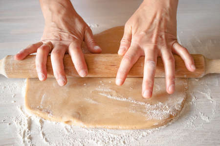 Female hands housewife with wedding ring roll out dough wooden rolling pin on white table background