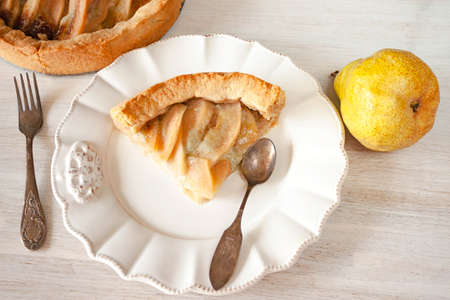 Pears fruit and blue cheese pie quiche piece, slice on plate on rustic white table, spoon, fork. Close up. 写真素材 - 157021682