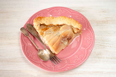 Pears and blue cheese pie quiche cake piece, slice on pink plate on rustic white table, fork.