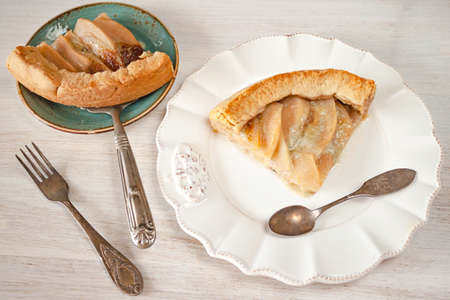 Pears and blue cheese pie quiche piece, slice on plate on rustic white table, spoon, fork, shovel. 写真素材 - 157021690