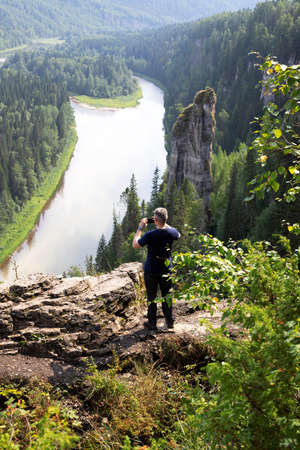 Caucasian man stands with his back turned and making photo of beautiful landscape of Devils finger or Rock Bloody finger on Usva river array Usvinskie pillars. Perm Krai. Russia 스톡 콘텐츠