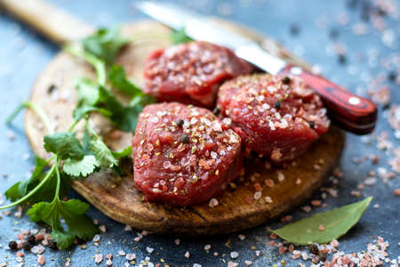 Raw meat beef steak on wooden cutting board, pink Himalayan salt, black pepper, bay leaf, cilantro, knife. Close up. Selective focus. Copy space 写真素材