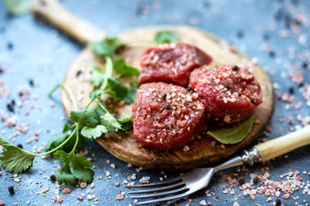 Raw meat beef steak on wooden cutting board, pink Himalayan salt, black pepper, bay leaf, cilantro, fork. Close up. Selective focus. Copy space