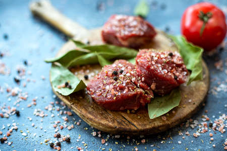 Raw meat beef steak on wooden cutting board, coarse pink Himalayan salt, black pepper, bay leaf, tomato. Close up. Selective focus. Copy space 写真素材