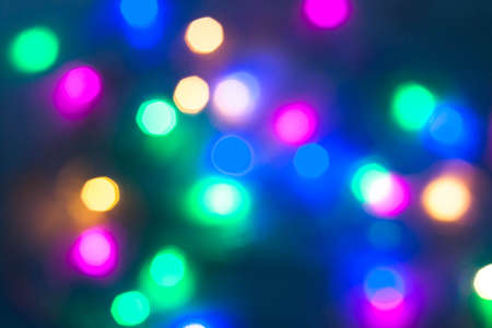 Abstract beautiful Christmas New Year garland multicolored neon ights close up blurred bokeh festive holiday dark background. Selective focus. Copy space