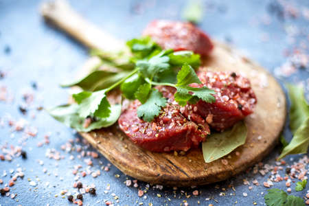 Raw meat beef steak on wooden cutting board, pink Himalayan salt, black pepper, bay leaf, cilantro. Close up. Selective focus. Copy space