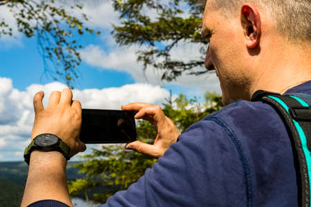 Caucasian man stands with his back turned and making photo of natural scenery landscape background. Close up. Selective focus. Copy space