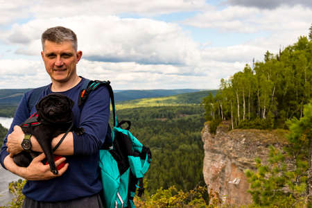 Man tourist standing smiling with dog black pug on natural scenery forest landscape background of Vetlan sheer cliff stone rocks panoramic view Krasnovishersk, Perm region, Russia. Copy space