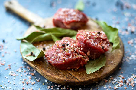 Raw meat beef steak on wooden cutting board, coarse pink Himalayan salt, black pepper, bay leaf. Close up. Selective focus. Copy space 写真素材