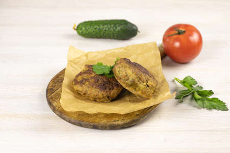 Homemade meat beef burger patties cutlet on on cutting board, baking paper on white table background with vegetables, herb. Low carb diet concept. Close up. Selective focus. Copy space