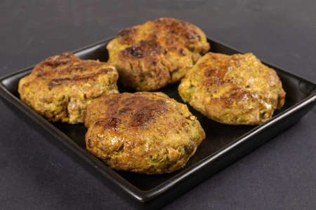Homemade meat beef burger patties cutlet heap on black plate table background. Keto diet concept. Close up. Selective focus. Copy space